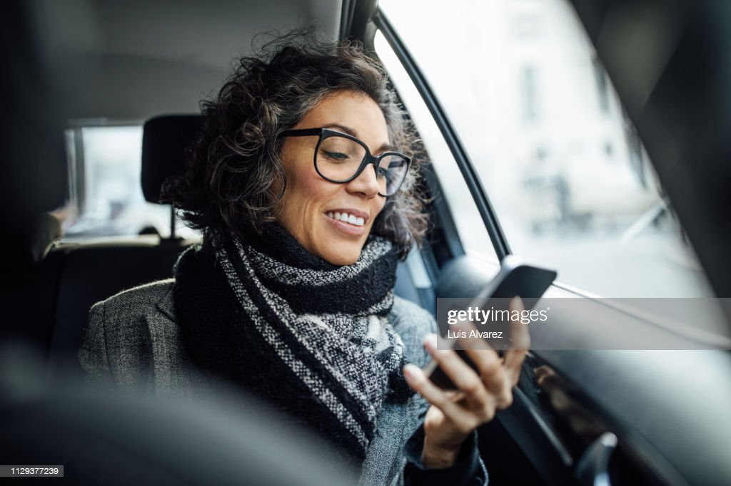 Mature businesswoman using phone while traveling by a taxi : Stock Photo