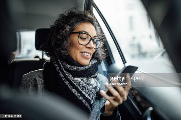 mature businesswoman using phone while traveling by a taxi - draagbare informatie apparatuur stockfoto's en -beelden