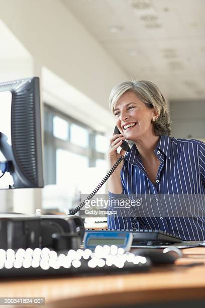 Mature businesswoman using telephone in office, smiling