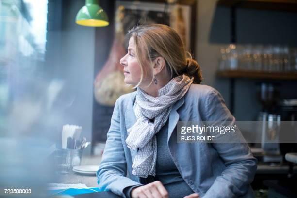 Mature businesswoman waiting in restaurant window seat