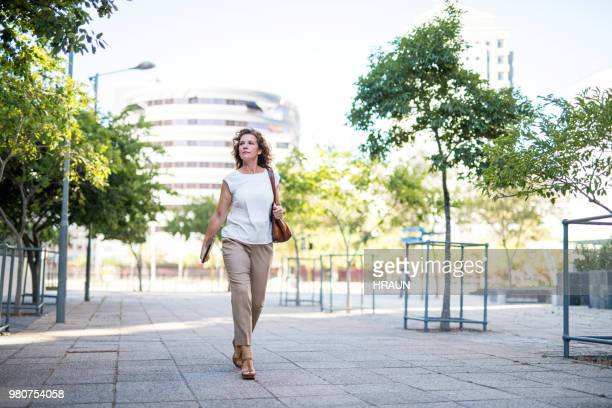 mature businesswoman walking on footpath in city - white purse stock pictures, royalty-free photos & images