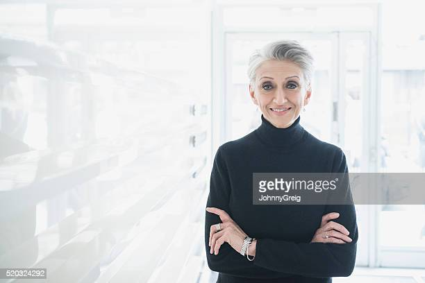 mature businesswoman wearing black sweater in modern office - turtleneck stock pictures, royalty-free photos & images