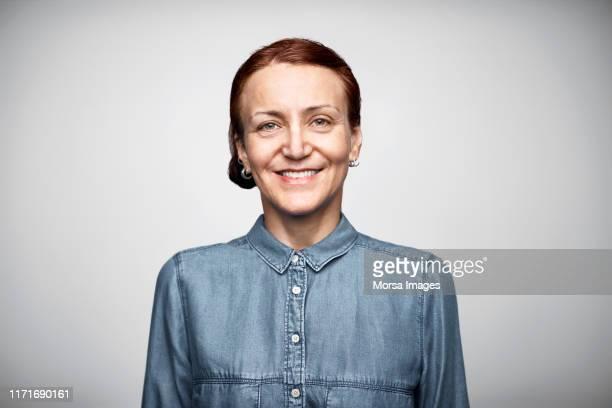 mature businesswoman wearing denim shirt - mature woman fotografías e imágenes de stock