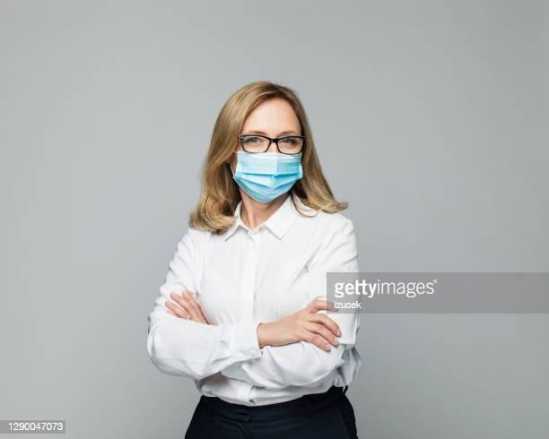 mujer de negocios madura que lleva máscara protectora de la cara - izusek fotografías e imágenes de stock