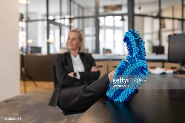 mature businesswoman with feet on desk wearing cleansing slippers in office - konzepte und themen stock-fotos und bilder