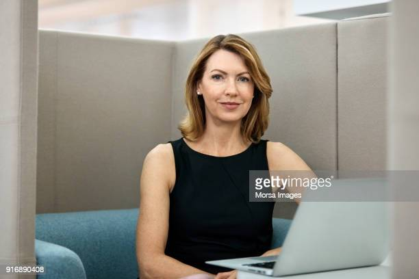 mature businesswoman with laptop in office - mid length hair stock pictures, royalty-free photos & images