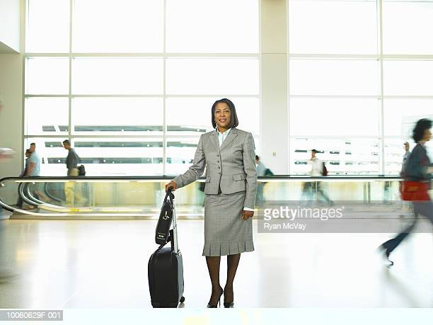 mature businesswoman with luggage standing in airport corridor - older women in short skirts stock pictures, royalty-free photos & images