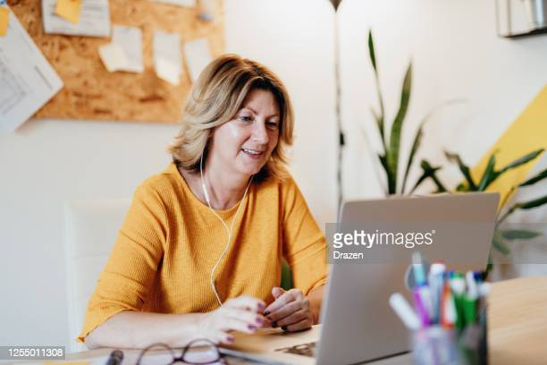 mature businesswoman working from home and attending video conference meeting - web conference stock pictures, royalty-free photos & images