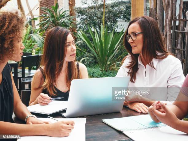 Mature businesswoman working in casual environment with her colleagues