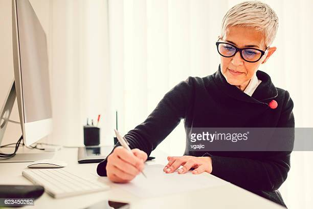 mature businesswoman working in her home office. - message stock pictures, royalty-free photos & images