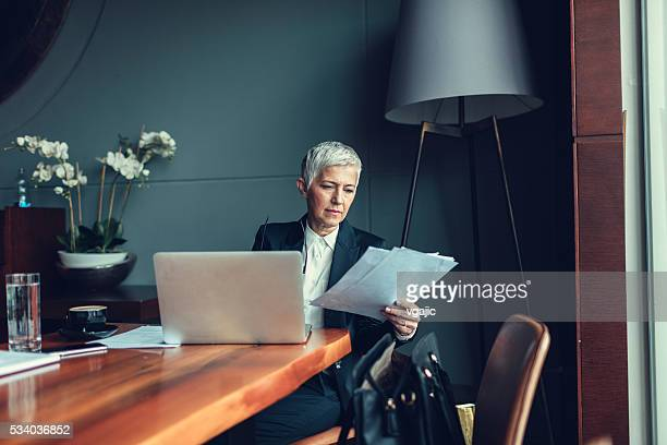 mature businesswoman working in her office. - business finance and industry stock pictures, royalty-free photos & images