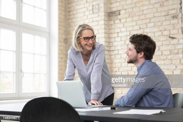 mature businesswoman working with younger colleague in office - doing a favor stock pictures, royalty-free photos & images