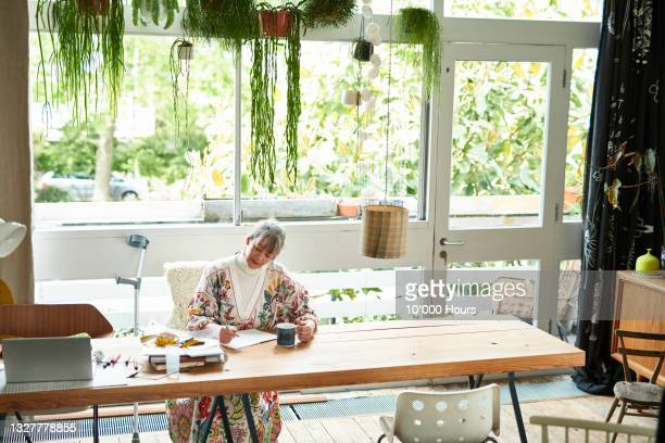mature businesswoman writing notes at dining table - greater london stock pictures, royalty-free photos & images