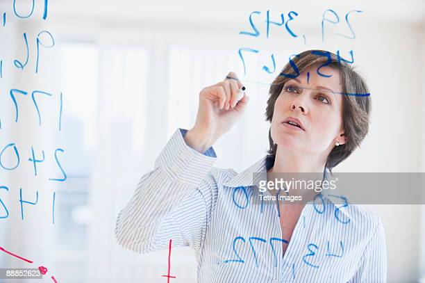 Mature businesswoman writing numbers on transparent glass wall