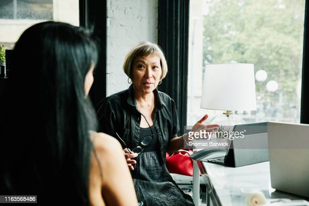 mature businesswomen discussing project at desk in creative office - disruptagingcollection fotografías e imágenes de stock