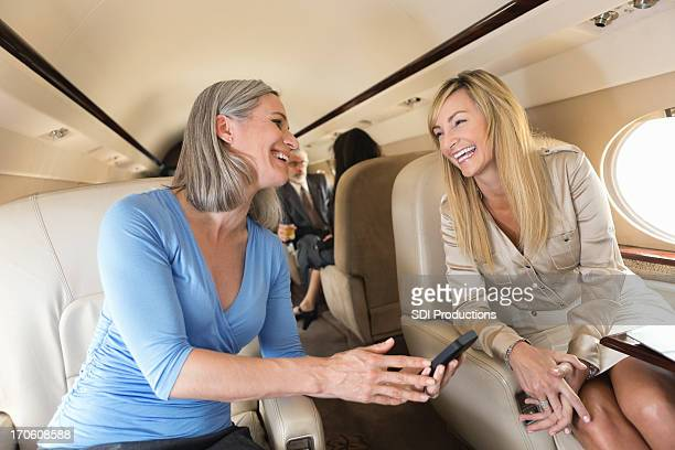 Mature businesswomen talking while on board private corporate jet