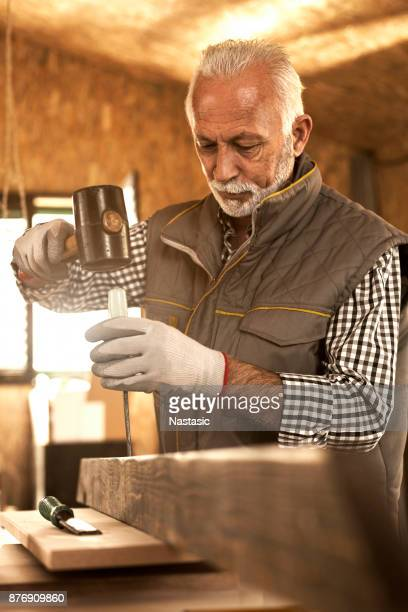 mature carpenter using hammer - work glove stock photos and pictures