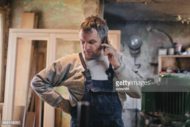 volwassen timmerman via telefoon - mid adult men stockfoto's en -beelden