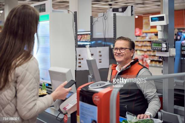 Mature cashier looking at woman paying through contactless payment in supermarket