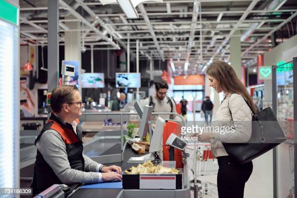 mature cashier looking at woman paying through technology at checkout counter in supermarket - kassierer stock-fotos und bilder