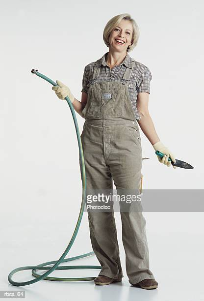 mature caucasian adult female wearing a checked blouse and gray overalls holds a garden hose and a small gardening shovel as she stands and smiles happily at the camera