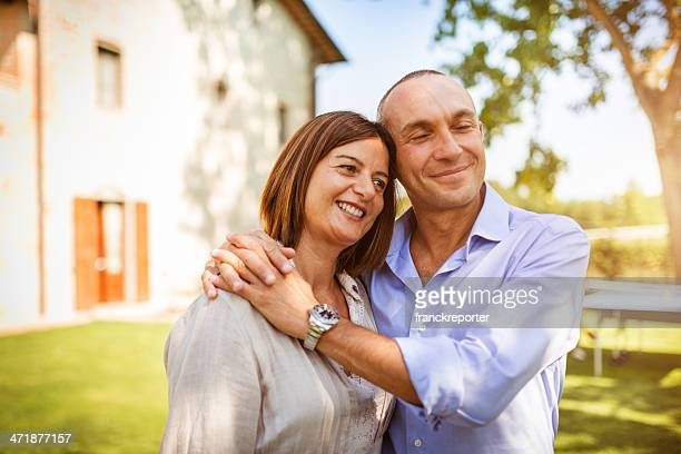 mature caucasian couple embracing in front of own house