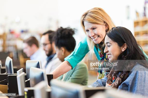 Mature Caucasian female professor assisting adult student in college library