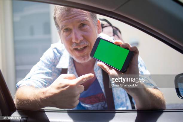 mature caucasian man asking direction from a car driver using smartphone - omar shamsuddin stock pictures, royalty-free photos & images