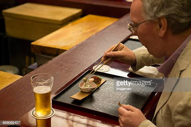 Mature Caucasian man eating Japanese dishes