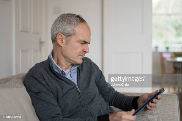 mature caucasian man frowning at his tablet device with concern - candid forum stock pictures, royalty-free photos & images