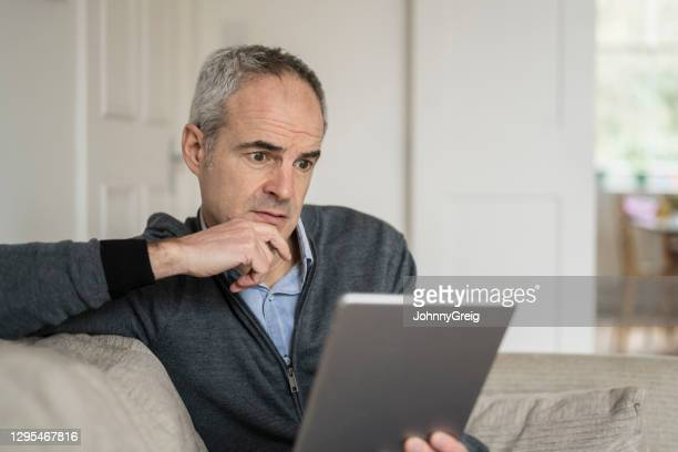 mature caucasian man looking at his tablet device with surprised and worried - candid forum stock pictures, royalty-free photos & images