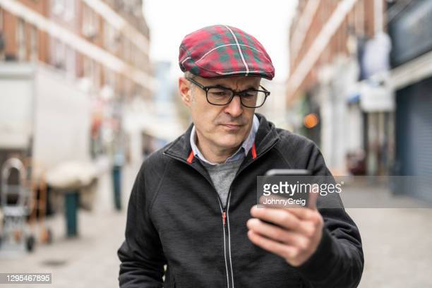 mature caucasian man looking concerned using smartphone - candid forum stock pictures, royalty-free photos & images