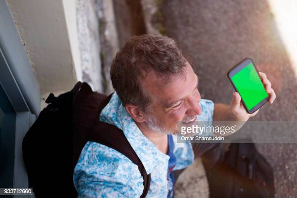 mature caucasian man showing a green screen handheld smartphone - omar shamsuddin stock pictures, royalty-free photos & images