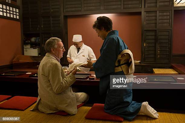Mature Caucasian man taking hot towel from Japanese hostess