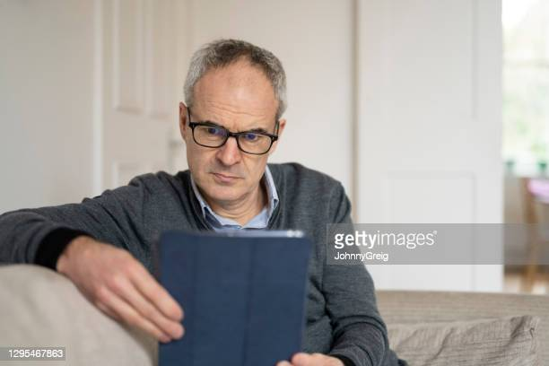 mature caucasian man using tablet device looking concerned - candid forum stock pictures, royalty-free photos & images