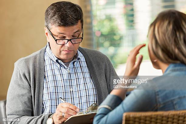 Mature Caucasian therapist meets with female patient