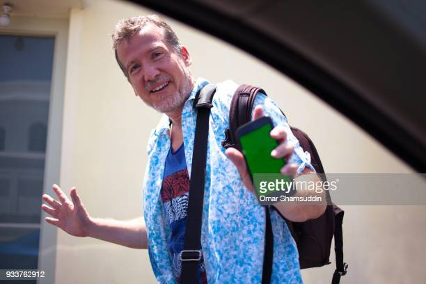 mature caucasian tourist with smartphone stop by a car - omar shamsuddin stock pictures, royalty-free photos & images