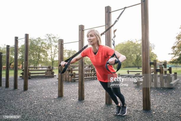 mature caucasian woman doing suspension training chest press - clapham common stock pictures, royalty-free photos & images