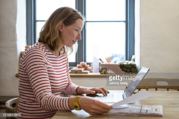 mature caucasian woman organizing business data on laptop - femalefocuscollection stock pictures, royalty-free photos & images