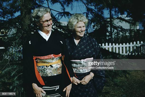 Mature Caucasian women Christian missionaries wearing silk kimonos smiling and posing for a photograph in front of evergreen trees both looking off...