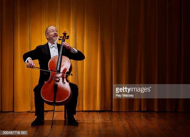 mature cellist playing on stage infront of curtains - musician stock-fotos und bilder