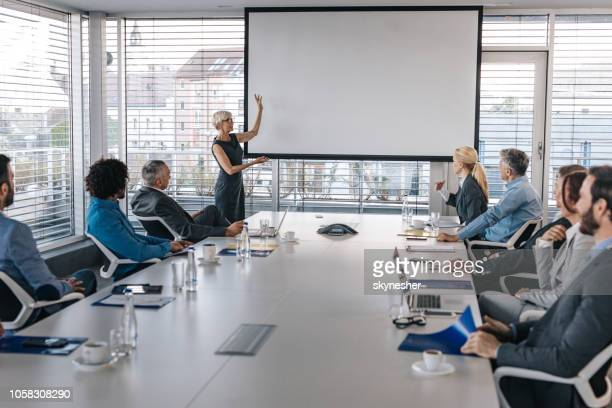 mature ceo giving a business presentation through projection screen in a board room. - projection screen stock pictures, royalty-free photos & images