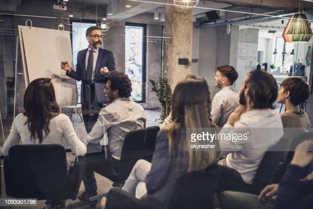 mature ceo giving his team a business presentation in a board room. - attending stock pictures, royalty-free photos & images