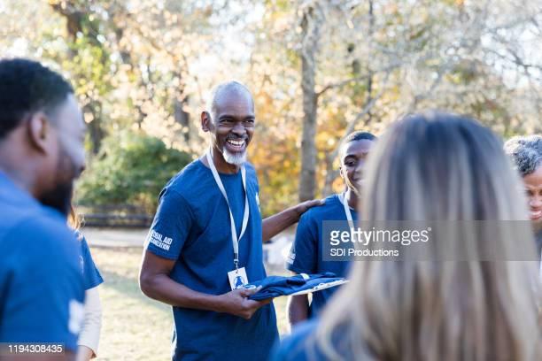 volwassen liefdadigheid evenement organisator praat met vrijwilligers - liefdadigheidswerk stockfoto's en -beelden