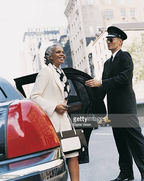 Mature Chauffeur Holding the Door of a Car Open for a Female CEO, Manhattan, New York, USA