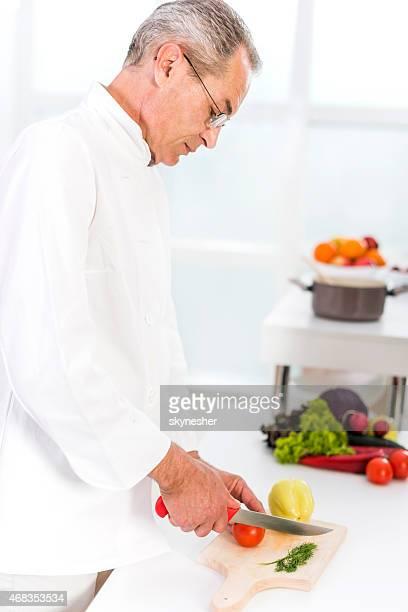Mature chef preparing food in the kitchen.