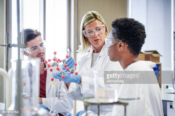 Mature chemistry teacher holding molecular model, students listening