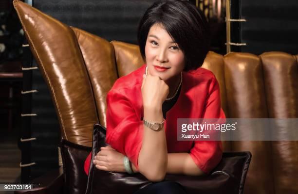 mature chinese businesswoman sitting on sofa - 上流社会 ストックフォトと画像