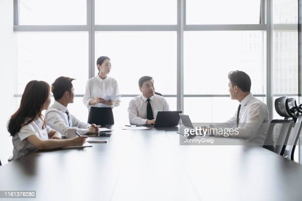 mature chinese ceo speaking with associates in boardroom meeting - formal businesswear stock pictures, royalty-free photos & images