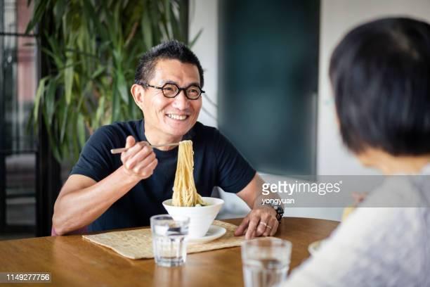 成熟した中国人男性は彼の妻と麺を食べます - 麺 ストックフォトと画像
